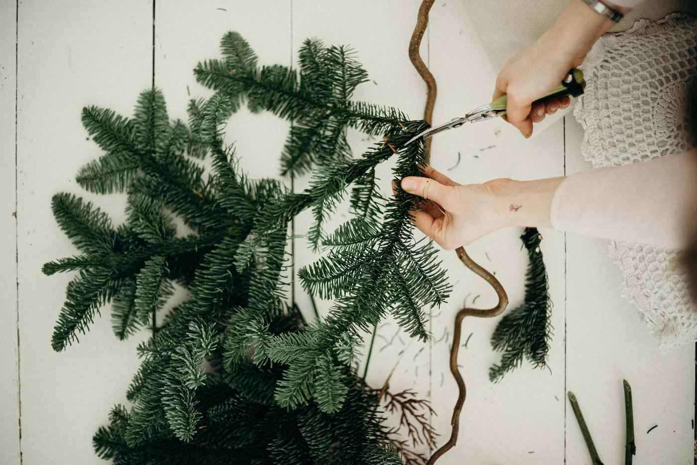 woman cutting fir bough - bring natural greenery in for the holidays